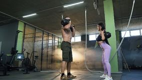 Attractive fit couple squatting with kettlebells in the hands in crossfit gym. stock video footage