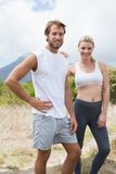 Attractive fit couple standing on mountain trail smiling at camera Stock Image