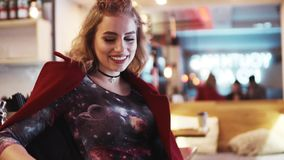 Attractive fit European girl in a red coat stands by the bar, and shares a bright smile towards the camera. Gorgeous stock footage