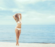 Attractive, fit girl in white bikini posing on the beach. Royalty Free Stock Image