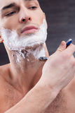 Attractive fit guy shaves his beard stock photo