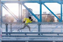 Attractive fit man running fast along modern bridge stock image