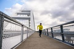 Attractive fit man running fast along modern bridge stock photography