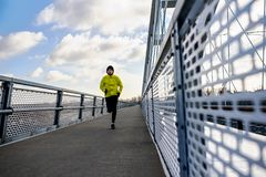 Attractive fit man running fast along modern bridge royalty free stock photography