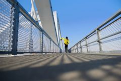 Attractive fit man running fast along modern bridge stock images