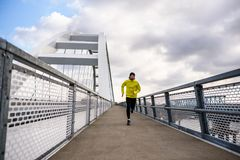 Attractive fit man running fast along modern bridge stock photo