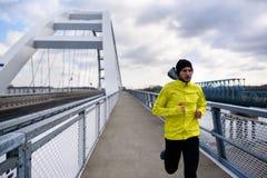 Attractive fit man running fast along modern bridge stock photos