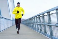Attractive fit man running fast along modern bridge royalty free stock images