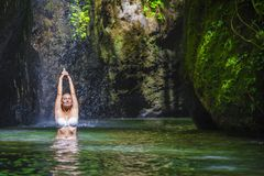 Attractive and fit tourist Caucasian woman practicing yoga exercise pose in amazing tropical exotic waterfall lagoon with green tu Stock Photos