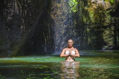 Attractive and fit tourist Caucasian woman practicing yoga exercise pose in amazing tropical exotic waterfall lagoon with green tu royalty free stock photography