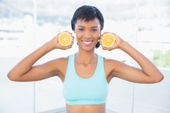Attractive fit woman holding two halves of an orange. In a living room stock images