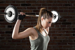 Attractive fit woman lifting dumbbells on brick background Royalty Free Stock Photos