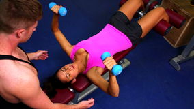 Attractive fit woman lifting dumbbells lying on exercise device. Being controlled by coach stock footage