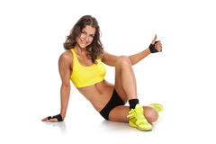 Attractive fit women sitting, smiling and showing thumbs up Stock Photo