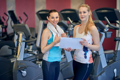 Attractive fit young female athlete with her personal trainer. Holding their training plan conceptual of planning and strategy before success and achievement Stock Photo