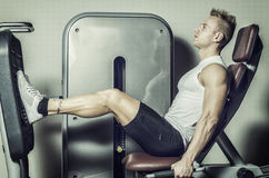 Attractive and fit young man in gym working out legs Stock Image
