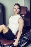 Attractive and fit young man in gym working out legs Royalty Free Stock Images