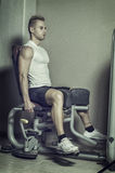 Attractive and fit young man in gym working out legs Stock Images