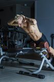 Attractive and fit young man in gym working out legs Royalty Free Stock Image