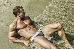 Attractive and fit young man smiling, lying down on the beach sand Royalty Free Stock Photos