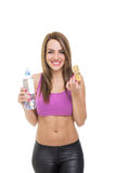 Attractive fit young woman having a healthy snack. Attractive fit young Caucasian blonde woman holding a granola cereal bar and bottle of water smiling isolated Stock Photography