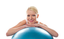 Attractive fit young woman resting chin over ball Stock Photo