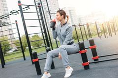 Attractive fit young woman in sport wear drink water and rest on the street workout area. The healthy lifestyle in city concept. Attractive fit young woman in royalty free stock images
