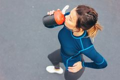 Attractive fit young woman in sport wear drink water and rest on the street workout area, view from top. The healthy lifestyle in. Attractive fit young woman in royalty free stock photography