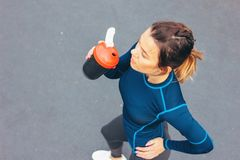 Attractive fit young woman in sport wear drink water and rest on the street workout area, view from top. The healthy lifestyle in. Attractive fit young woman in royalty free stock image
