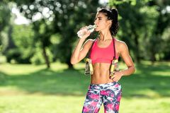 Attractive fitness athlete woman drinking water after workout exercising on sunset evening summer. royalty free stock images