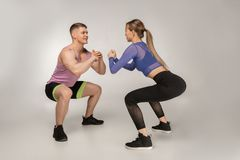 Attractive fitness coach shows the beautiful girl how to do sguats royalty free stock image