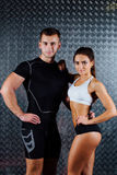 Attractive fitness couple indoor portrait. Attractive fitness couple indoor portrait, trained female body, studio caucasian model. Grey metal surface with a royalty free stock images