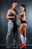 Attractive fitness couple indoor portrait. Attractive fitness couple indoor portrait, trained female body, studio caucasian model. Grey metal surface with a stock images