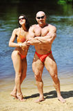 Attractive fitness couple posing on a beach Royalty Free Stock Image