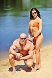Attractive fitness couple posing on a beach Royalty Free Stock Photo
