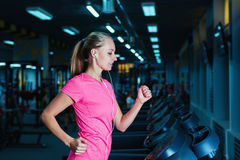 Attractive fitness girl running on machine treadmill. Pretty girl doing workout at modern fitness gym. Stock Photo
