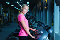 Attractive fitness girl running on machine treadmill. Pretty girl doing workout at modern fitness gym. Stock Photos