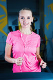 Attractive fitness girl running on machine treadmill. Pretty girl doing workout at modern fitness gym. Royalty Free Stock Images