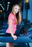 Attractive fitness girl running on machine treadmill. Pretty girl doing workout at modern fitness gym. Royalty Free Stock Image