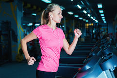 Attractive fitness girl running on machine treadmill. Pretty girl doing workout at modern fitness gym. Royalty Free Stock Photos