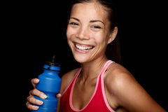 Attractive fitness sportswoman on black background. Smiling fitness sportswoman with a blue sport bottle on black background. Multiracial Asian fitness model Stock Images