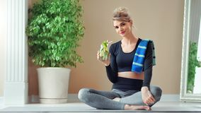 Attractive fitness woman drinking refreshing cocktail after gym training sitting in lotus position. Full shot. Smiling relaxed sport female posing having stock video footage