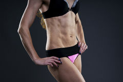 Attractive fitness woman on gray background in studio. Muscular abdomen close-up Stock Photography