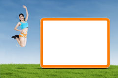 Attractive fitness woman jumping with blank board Royalty Free Stock Photo