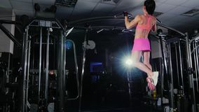 Attractive fitness woman pulls on the bar in the gym. Female bodybuilding. Side view.  stock video
