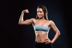 Attractive fitness woman is showing her biceps on black background. Attractive fitness woman, trained female body, lifestyle portrait, caucasian model is showing stock photo