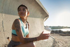 Attractive fitness woman sitting and resting after work out outdoors Royalty Free Stock Photos