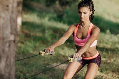 Attractive fitness young woman exercising with resistance band oudoor. Attractive fitness young woman exercising with resistance band oudoor Stock Images