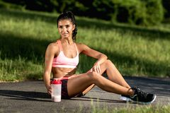 Attractive fitness young woman rest after exercises oudoor. Sporty woman holding protein shake after tranning. royalty free stock photos