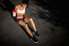 Attractive fitness young woman rest after exercises oudoor. Sporty woman holding protein shake after tranning. stock images